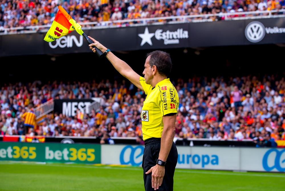 soccer referee raises flag