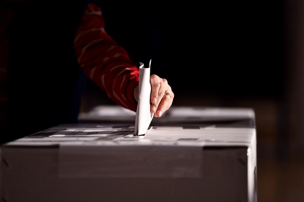 hand casting paper vote in ballot box