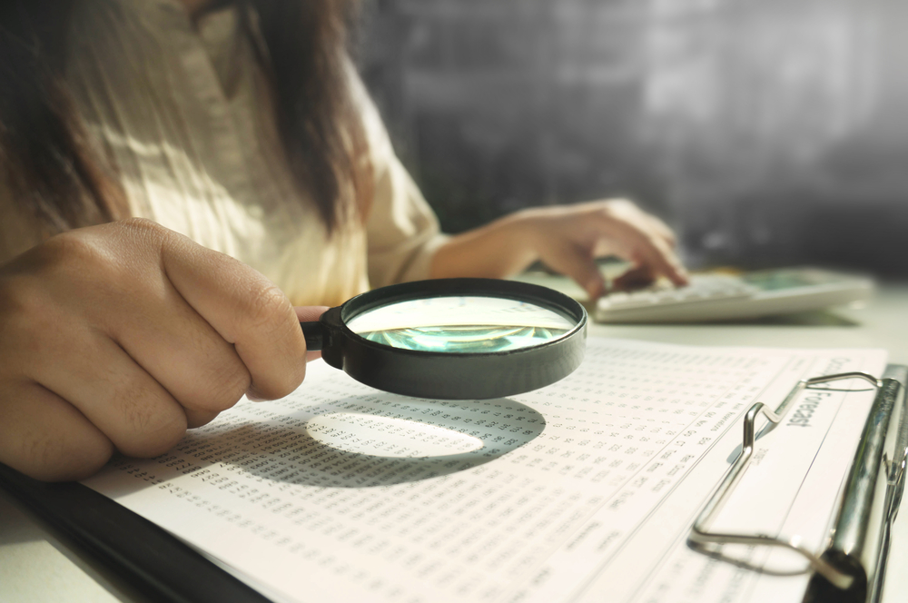 female using magnifying lens to investigate financial documents