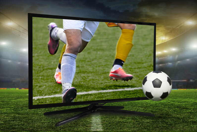 Soccer players and ball coming out of a TV