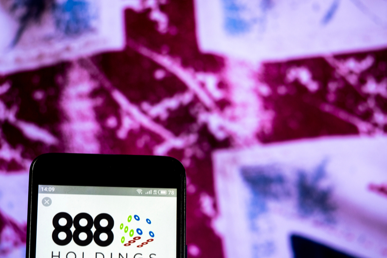 888 Holdings logo on a smartphone in front of UK flag