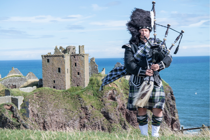 Bagpiper outside Dunnottar Castle in Stonehaven, Scotland