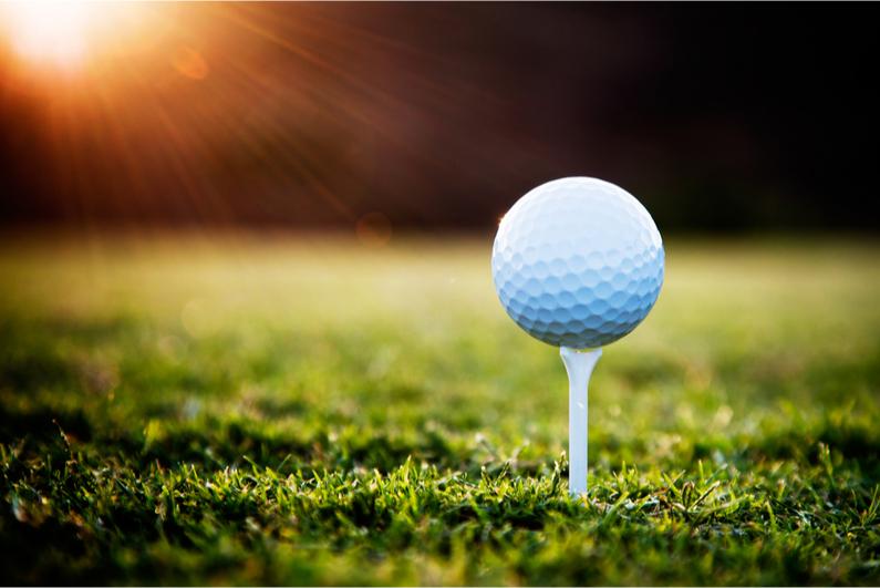 Closeup of a golf ball on a tee at sunset