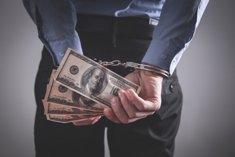 handcuffed man holding cash behind his back