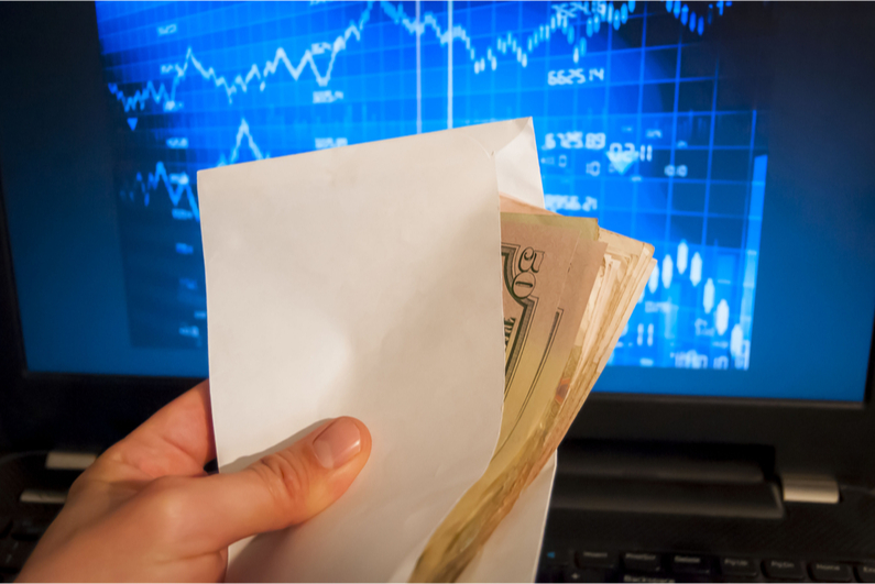 Person holding an envelope of money in front of a stock screen