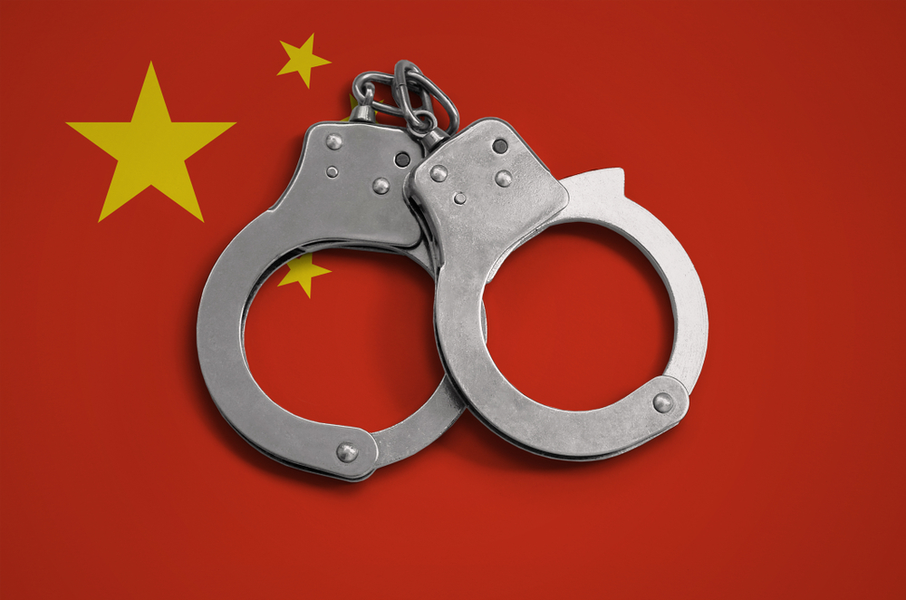 handcuffs against a China flag backdrop
