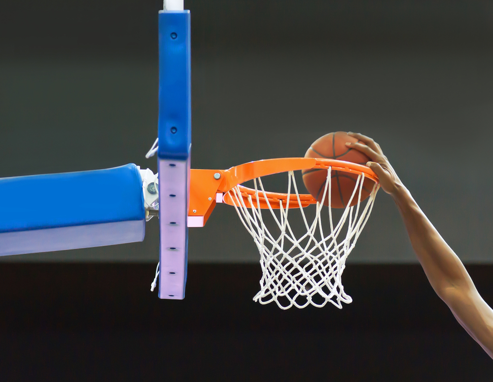 basketball player's arm throwing the ball into the hoop