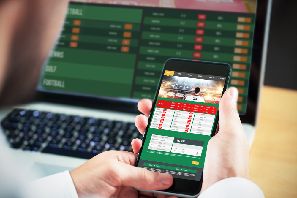 male holds cell phone to view sports betting results