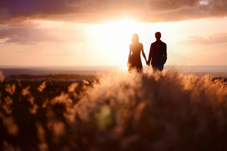 Young couple holding hands at sunset