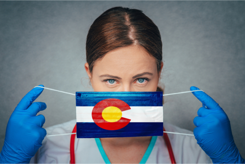 Female doctor putting on Colorado flag mask