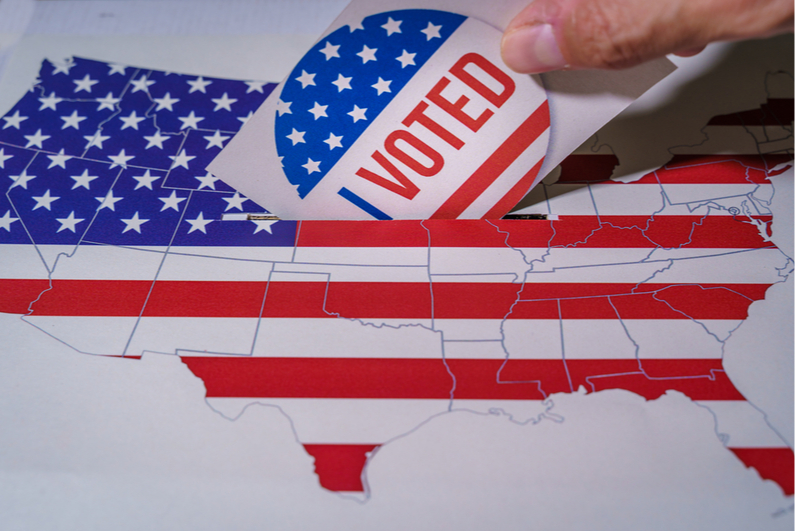 Person dropping a ballot into a ballot box with the map of the United States painted on it