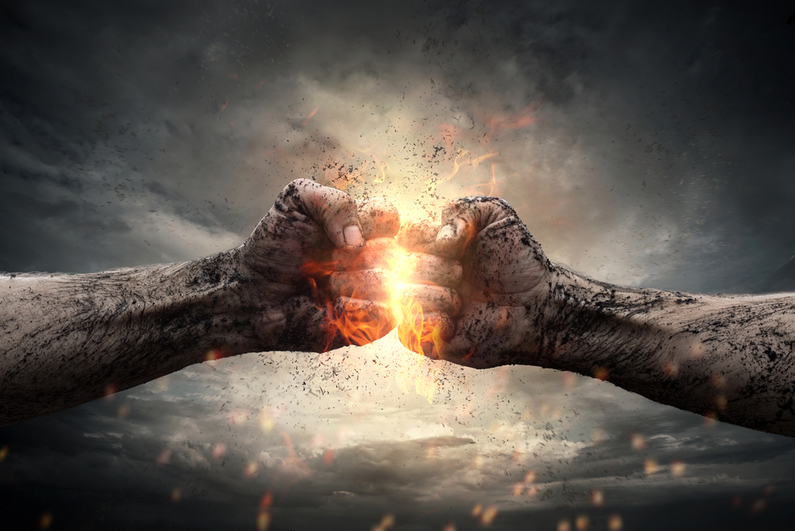 Two fists hitting each other under dramatic sky