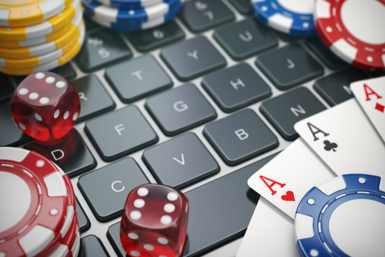Dice, cards, and chips on a laptop keyboard
