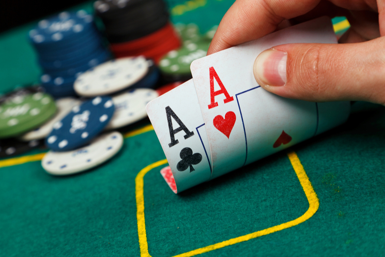 Poker player peeking at pocket Aces
