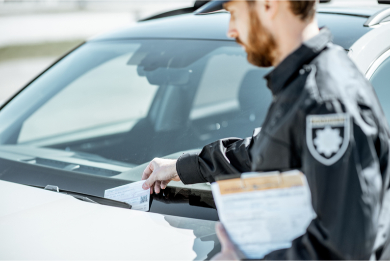 Police officer placing a ticket on a car windshield