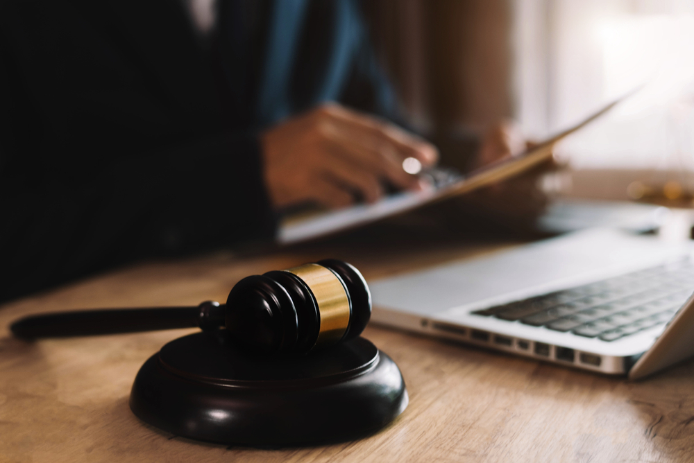 legal professional works at a desk with judge's gavel and laptop