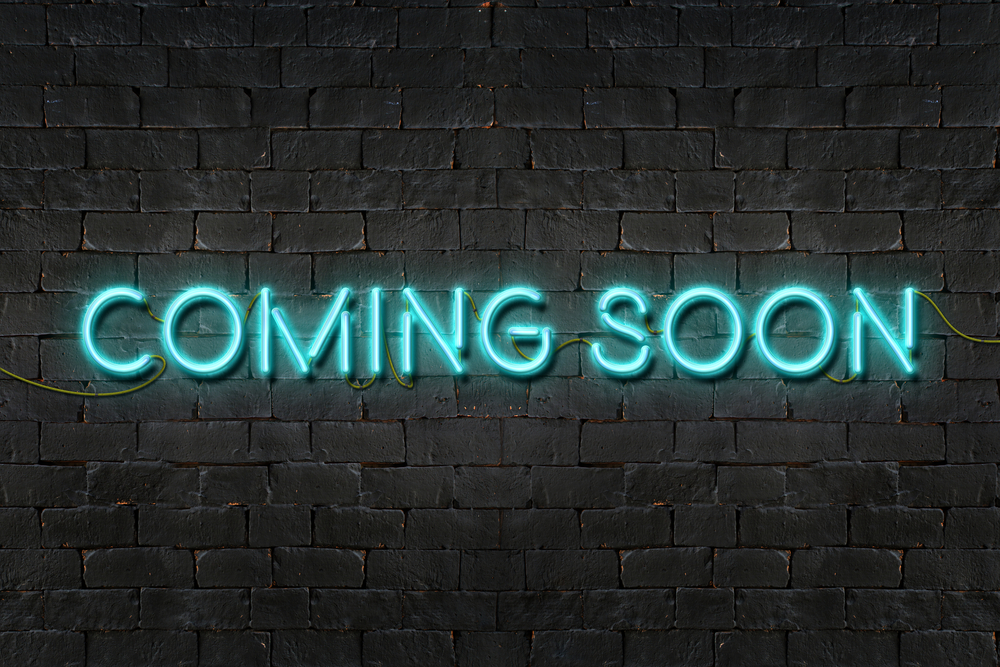 "blue neon sign against a brick-wall background reads ""coming soon"""