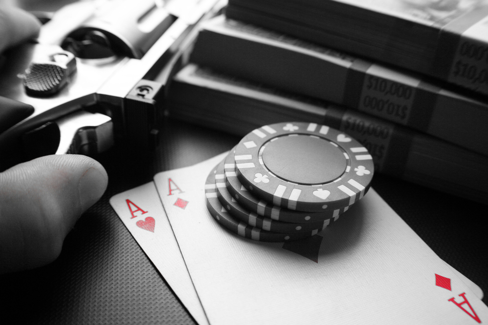 hand holding a gun next to stacks of money, poker cards and chips