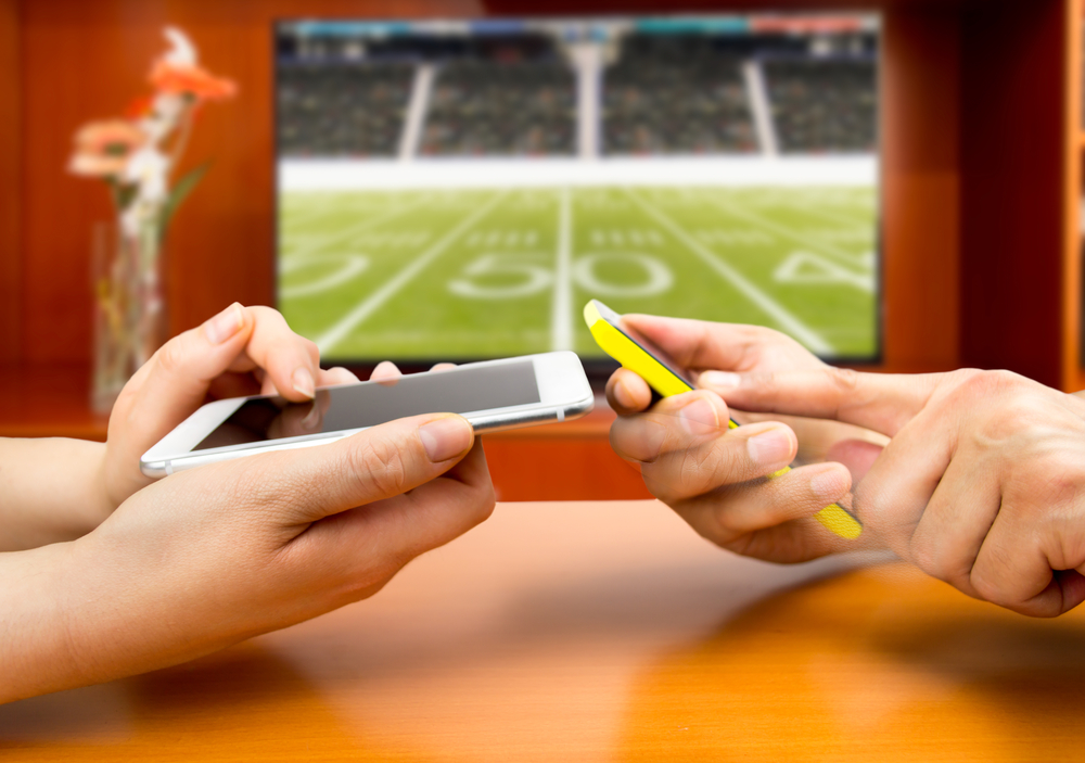 two people bet on their cell phones as a laptop screen shows an American football pitch