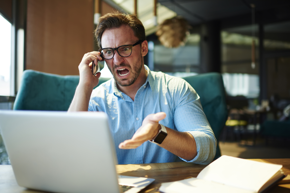 angry man speaks on a cellphone while sitting at a desk in front of a laptop