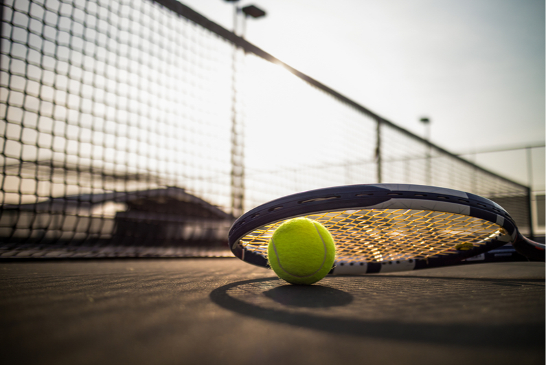 Tennis ball and racquet on a court