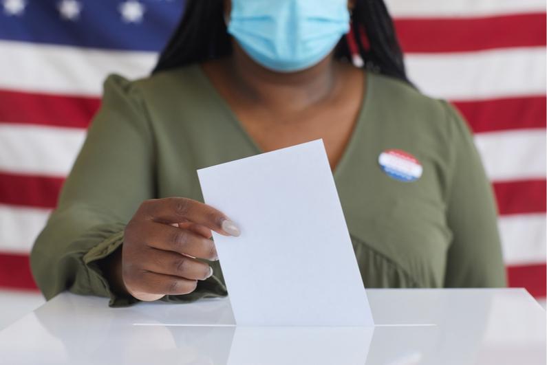 Woman wearing a protective mask placing a ballot in a ballot box