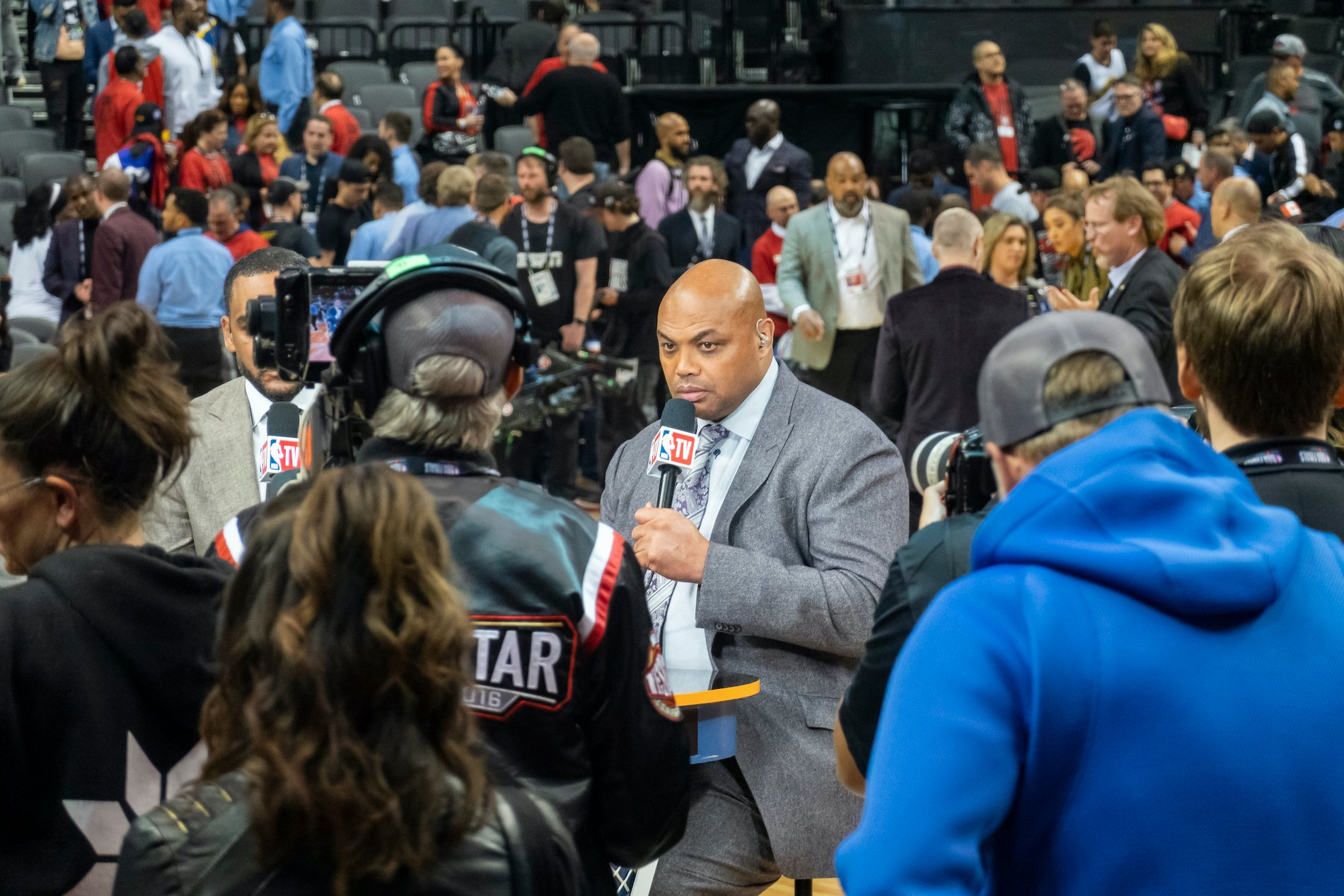 Charles Barkley holds a microphone surrounded by a crowd