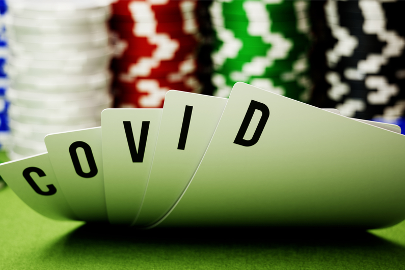 """Five poker hole cards spelling out """"COVID"""""""