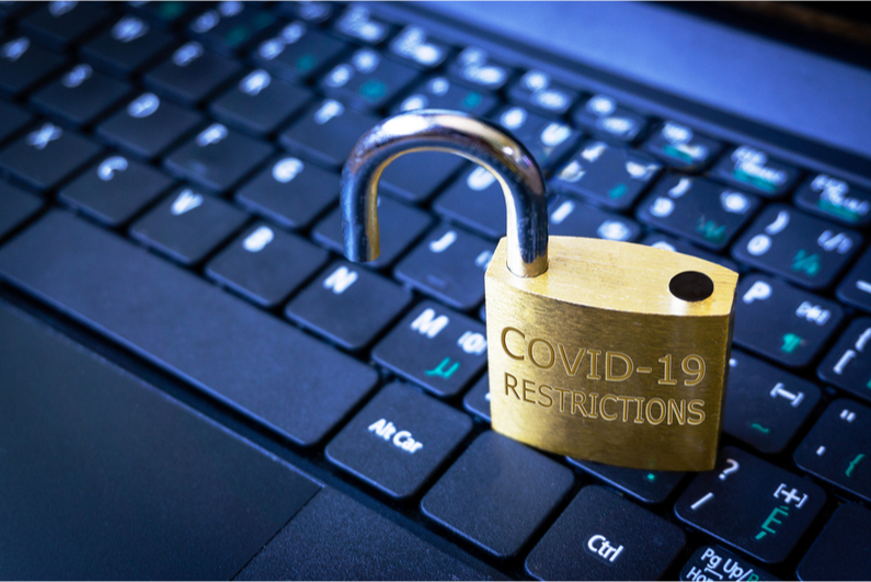 """Open padlock stamped with """"COVID-19 RESTRICTIONS"""" on a laptop keyboard"""