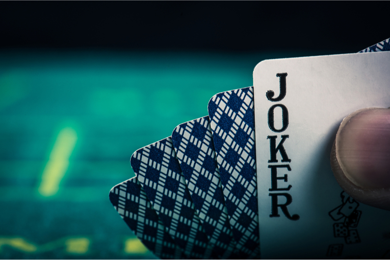 Poker player peeking at a Jokker in his hole cards