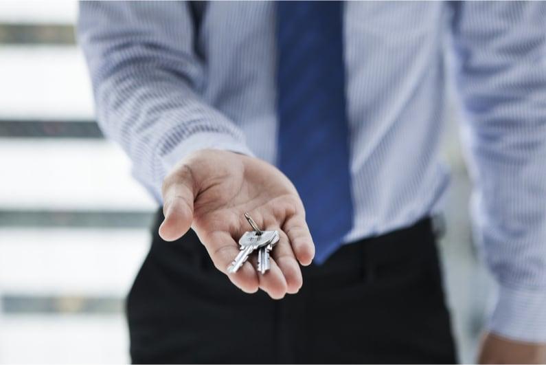 businessman handing over keys