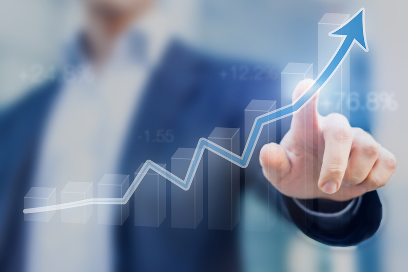 Businessman pointing to upward trending curve