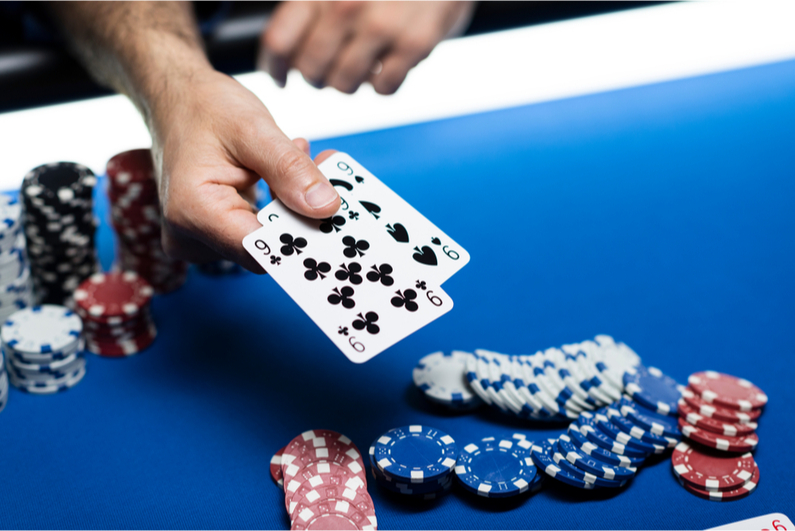 Man showing two black nines in a poker game