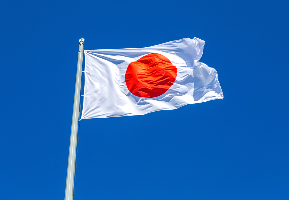 flag of Japan on a mast against a blue sky backdrop