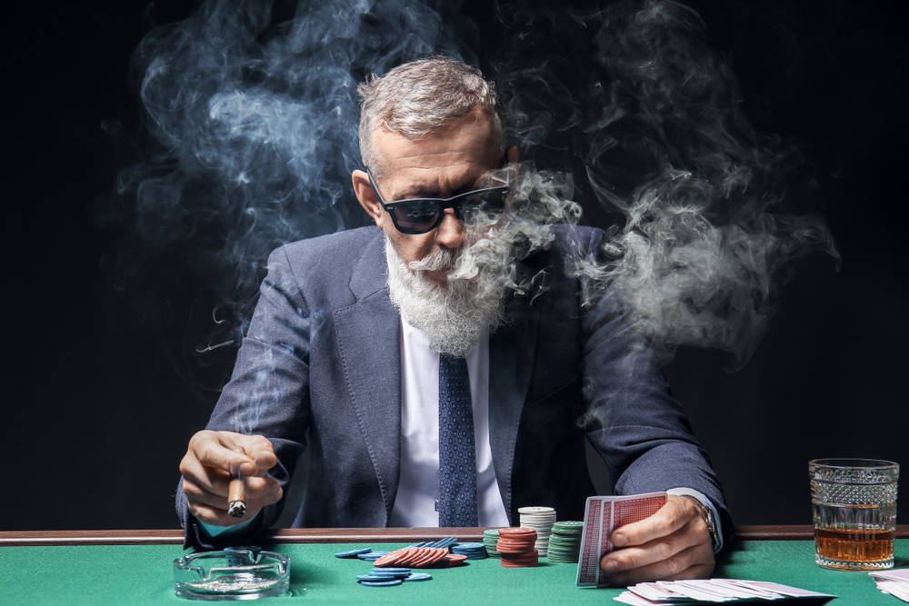 man in suit smoking cigar while at a gambling table