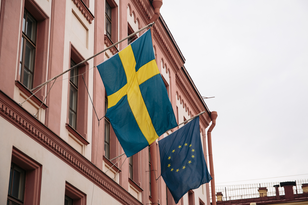 flag of Sweden and another of the EU hang outside a building