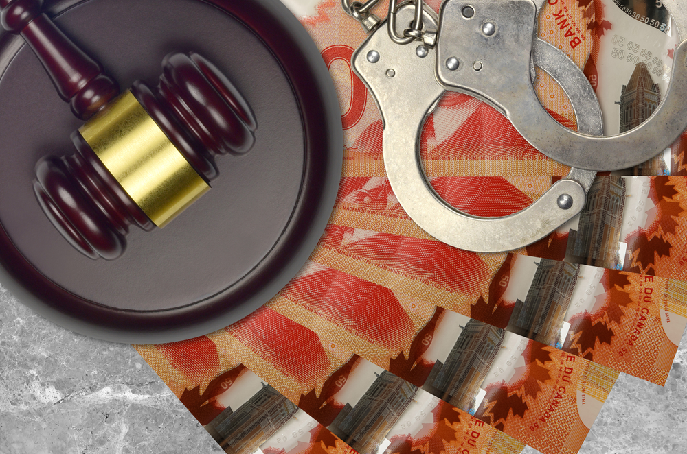 judge's gavel, handcuffs, and Canadian 50-dollar notes