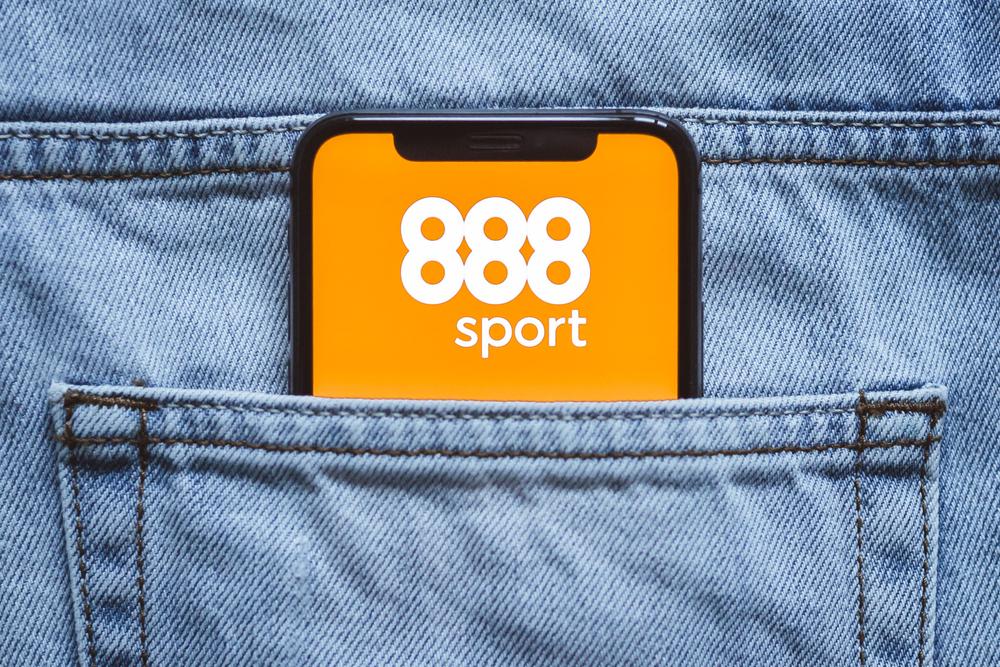 Smartphone inside jeans back pocket sporting the 888Sport logo