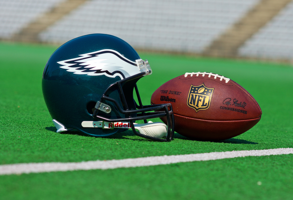 Philadelphia Eagles helmet and football on green pitch