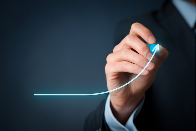 Businessman drawing an upward-sloping curve