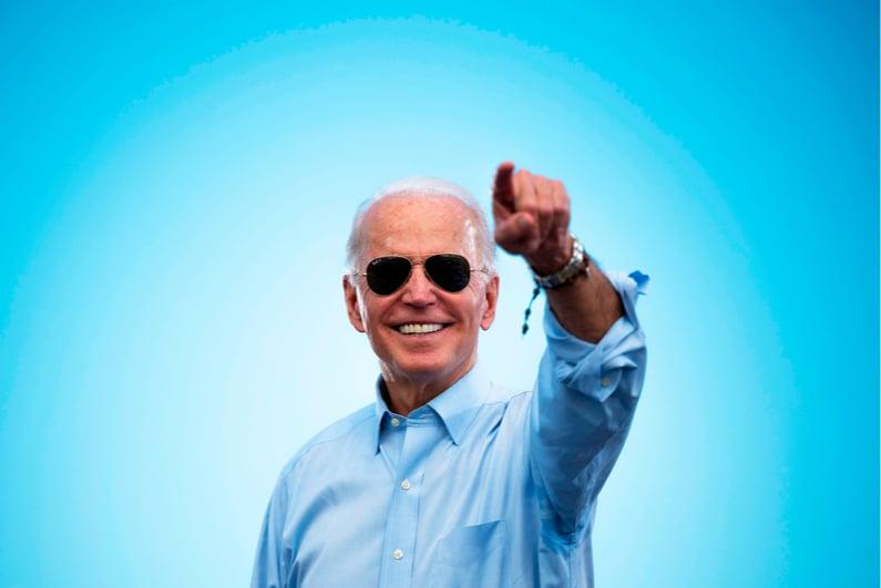 Joe Biden smiling against a sky blue background