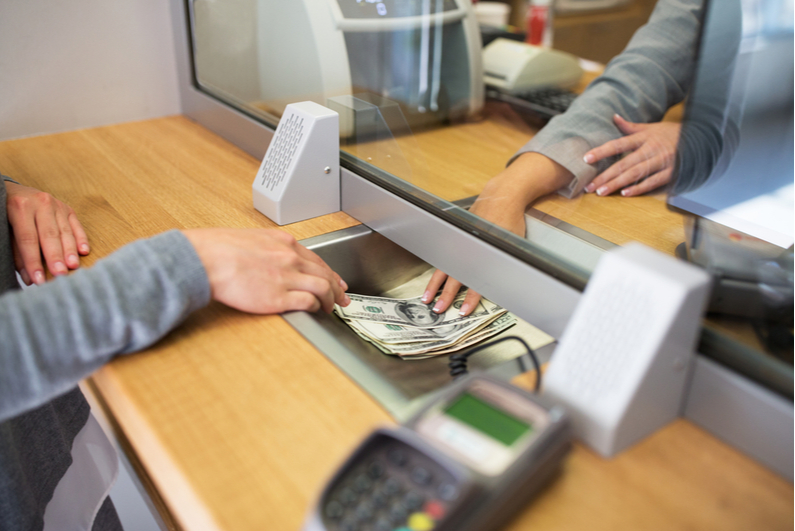 Person withdrawing money at a bank