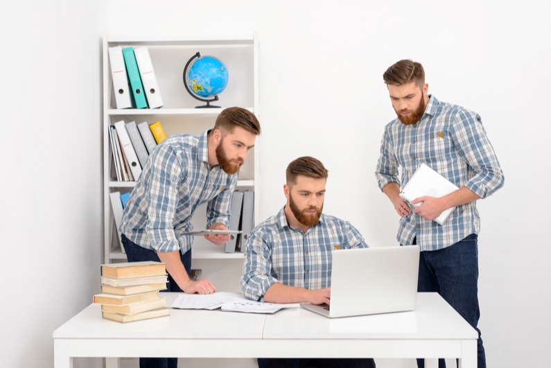 Three male clones looking at a laptop