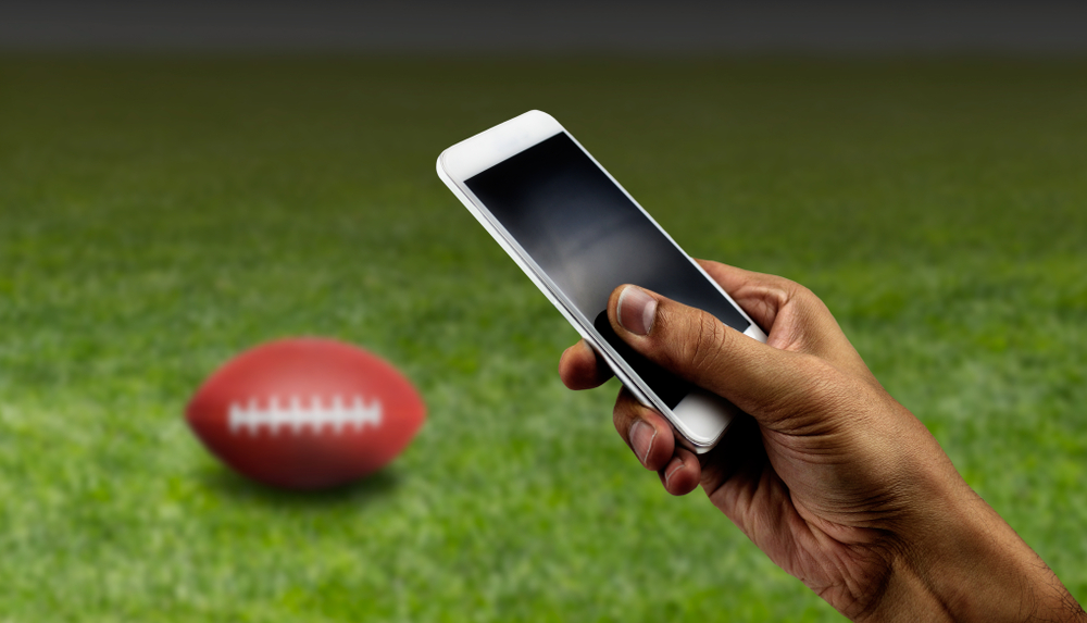 hand holds smartphone with an American football on a field in background