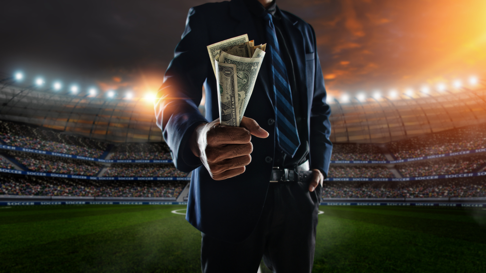 man in suit holding US dollar bills while standing in a soccer stadium