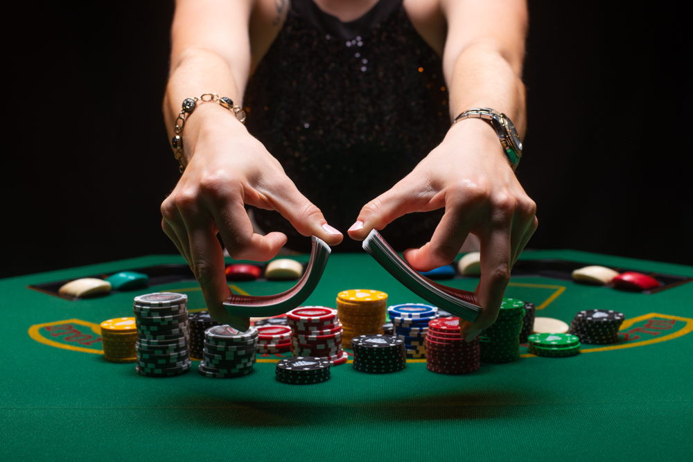 female croupier shuffling cards on poker table with chips