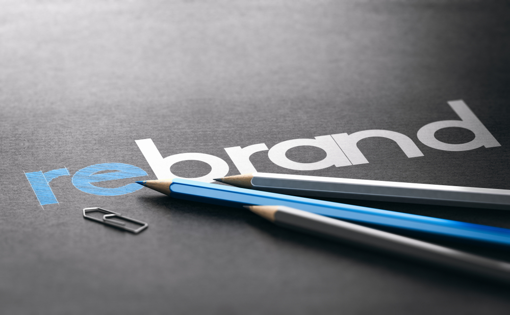 the word rebrand on a slate background, three pencils, and a paper clip