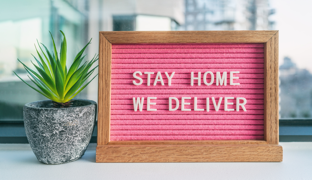 """Sign reads """"Stay Home We Deliver"""""""