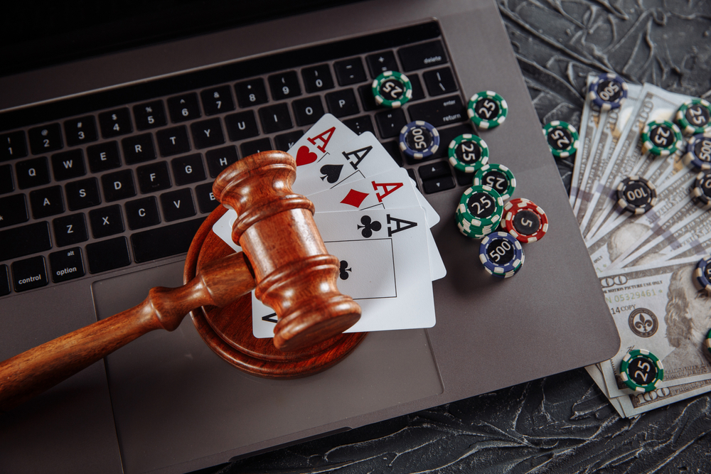 judge's gavel, Ace cards, poker chips, and US dollar bills with laptop in background