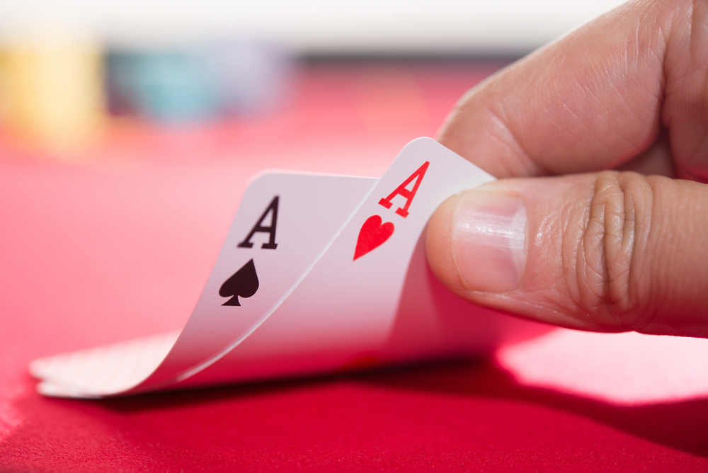 poker player lifts two Ace cards